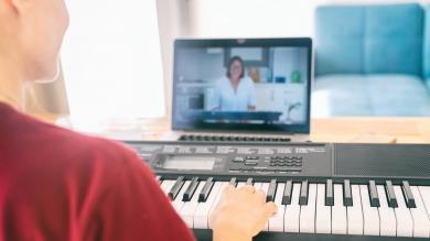 Young girl woman learns to play the piano with a teacher on a video conference from a laptop.