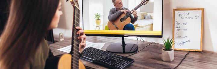 Girl taking guitar lesson online