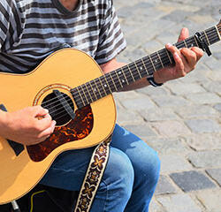 Person playing a guitar outdoors