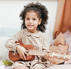 Young girl playing the ukulele